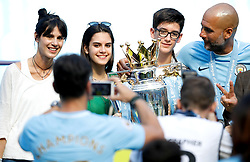 Pep Guardiola (right) celebrates with the trophy and wife Cristina Serra (left) and family