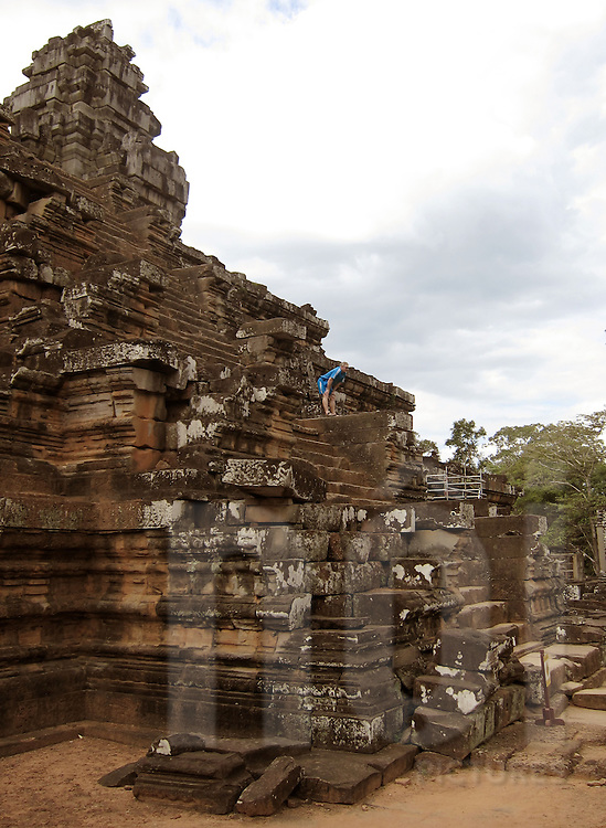 Tourist posing on ledge of ancient temple ruin, Angkor, Siem Reap, Cambodia, Southeast Asia