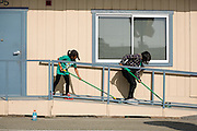 Sisters Jenina, 10, and Jessica Fernandez, 15, clean Curtner classroom exteriors during Comcast Cares Day at Curtner Elementary School in Milpitas, California, on April 27, 2013. (Stan Olszewski/SOSKIphoto)