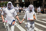 New York, NY - 25 June 2017. New York City Heritage of Pride March filled Fifth Avenue for hours with groups from the LGBT community and it's supporters.Marchers from Gays Against Guns dressed in white, with white veils over their heads, each bearing a card with the name, photograph, and history of a young gay or lesbian killed by guns. Commemorated by these two marchers are Christopher Drew Leinonen and Juan Ramon Guerrero, killed in the Pulse nightclub in 2016.
