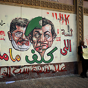 December 08, 2012 - Cairo, Egypt: A Protestor anti-president Mohamed Morsi stands beside a cartoon of president Morsi and the ex-president Mubarak, outside the presidential Palace in central Cairo...Sporadic clashes between supporters and opponents of president Mohamed Morsi, erupted in the past week over his assumption of extraordinary powers and the scheduling of a referendum on a disputed draft of the new constitution...Thousands of opposition protesters rallied outside the palace, in Cairo's Tahrir Square, and in cities and towns across the country, calling for an end to Mr Morsi's power grab and the shelving of the draft constitution. (Paulo Nunes dos Santos/Polaris)