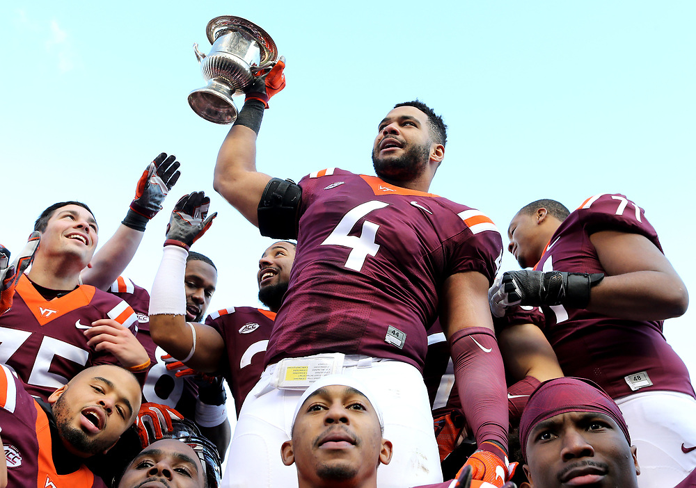 Nov 26, 2016; Blacksburg, VA, USA;  Virginia Tech Hokies defensive end Ken Ekanem (4) celebrates with the Commonwealth Cup after beating the Virginia Cavaliers at Lane Stadium. Mandatory Credit: Peter Casey-USA TODAY Sports