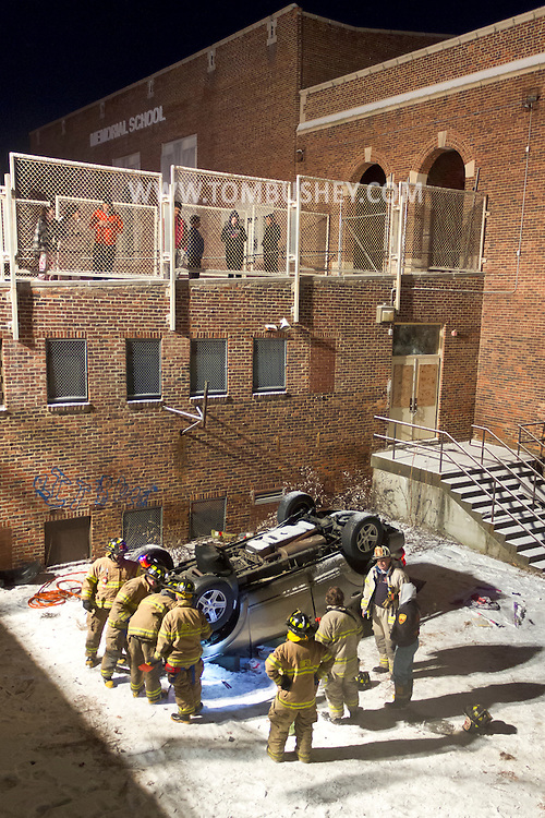 Middlletown, New York - Middletown firefighters and police work at the scene of a motor vehicle accident on Dec. 31, 2013. A vehicle went through a fence and landed upside down in a play area at the former Memorial School. A snow squall had left the roads very slippery.