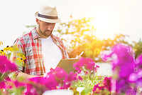 Portrait of mature male gardener writing report on clipboard over flowers in shop