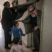 Mahmoud Abu Sbeih, 70, a palestinian refugee who escaped Syria with his family, leaves his room to take a walk, on december 21st 2013 in Cyber City.