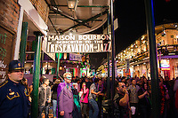 Revelers crowd Bourbon Street during Mardi Gras 2013 in New Orleans, Louisiana. A state police officer looks on.