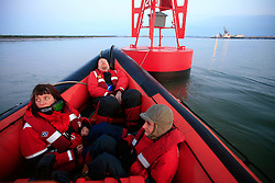UNITED KINGDOM MEDWAY 22JUN09 - Exhausted Greenpeace activists rest on an inflatable boat and a buoy after protesting against  coal delivery to Kingsnorth power station by boarding Sir Charles Parsons coal ship.....jre/Photo by Jiri Rezac / Greenpeace....© Jiri Rezac 2009