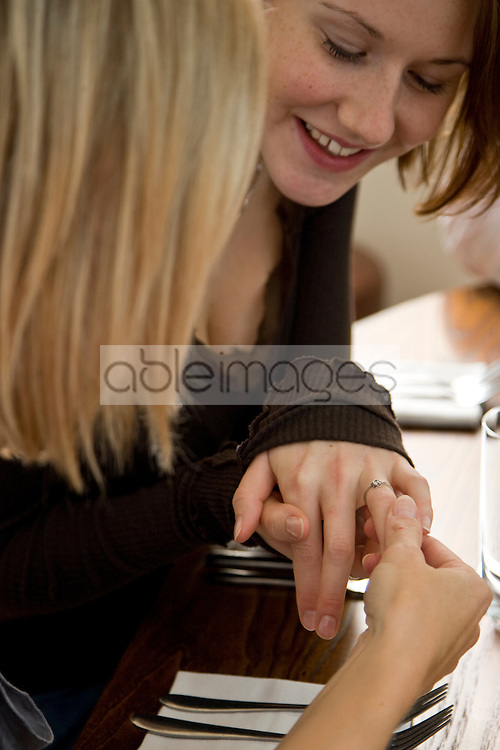 Close up of a woman sitting at a dining table showing her engagement ring to a girlfriend