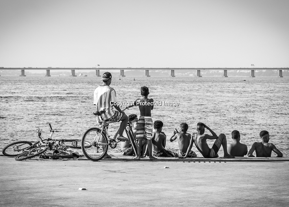 Young men relax at portside in Rio de Janeiro's Guanabara Bay with the bridge Rio-Niteroi in the background