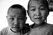 Two boys look at the camera in rural Mongolia.