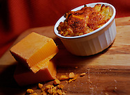 Blocks of cheddar cheese sit on a wooden cutting board beside a ramekin of gourmet, baked macaroni and cheese. (Photo by Carmen K. Sisson/Cloudybight)