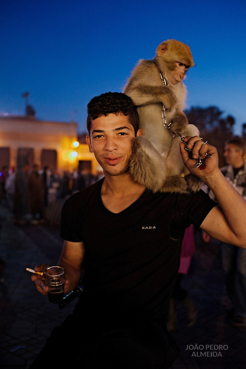 A street performer with his monkey at enjoying a short break.