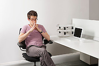Thoughtful young businessman sitting on office chair