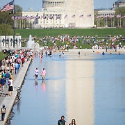 Visitors take advantage of warm weather to enjoy the newly renovated Lincoln Memorial Reflecting Pool on the National Mall in Washington DC. In the background is the base of the Washington Monument, with the dome of the US Capitol Building in the distance.