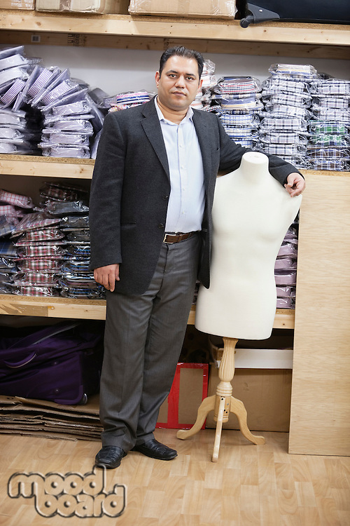 Portrait of male owner standing by tailor's dummy in clothing store