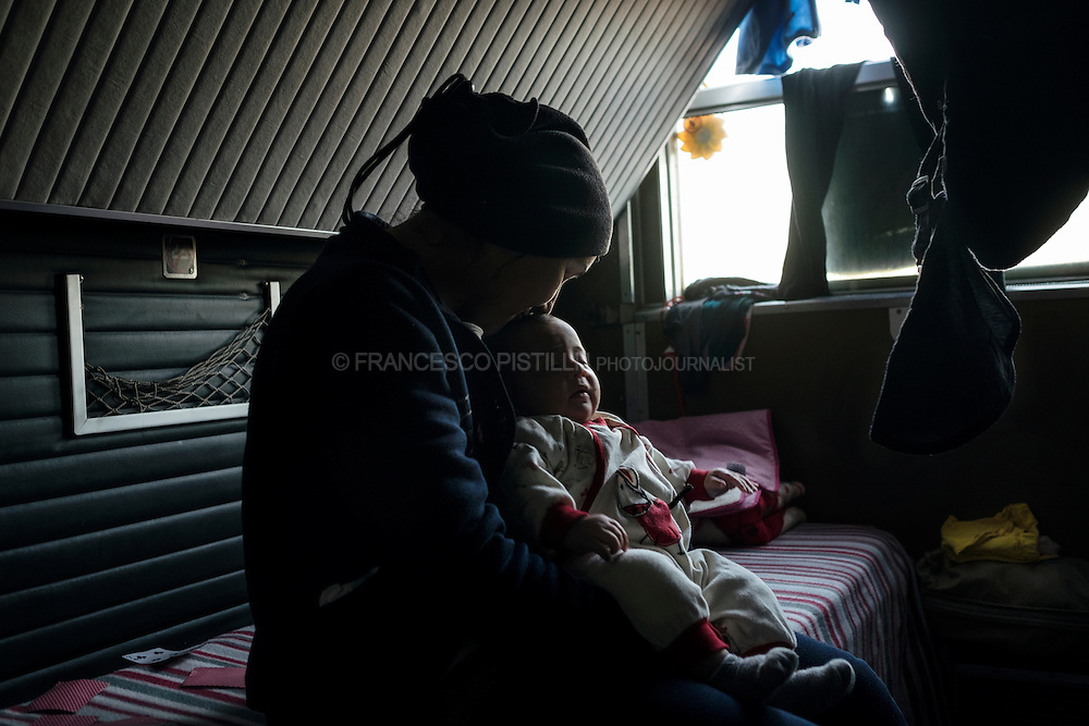 R. (32 yo, Syria) kissing her nephew, their are living in an abandoned train. Idomeni railway station - 12.000 refugees are living in small tents and the ruins of an old railway station in Idomeni.