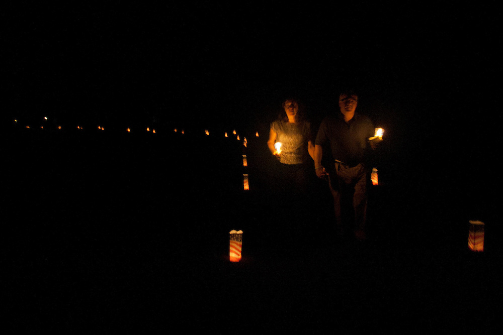 Tony and Debbie Mishik walk back from the 9/11 memorial during a Candle Light Vigil held at Chestnut Branch Park in Mantua Saturday September 10.