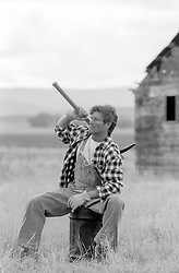 rugged good looking worker on a ranch sitting on a chair while carrying a heavy tool