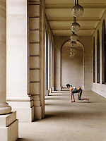 Female runner crouching in starting position in portico side view