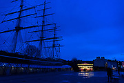 Lights of a carousel glowing in the winter dusk are dwarfed by the silhouette of the nearcy Cutty Sark, Greenwich, England.