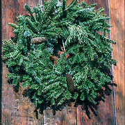 Christmas Wreath evergreen leave and pine cones decorations on front door in Greenwich Village.<br /> <br /> The tradition of hanging wreath during Christmas is essentially a Christian ritual. This is done during the Christmas season, traditionally used to prepare for the coming of Christ, also known as the Advent season in Christianity. <br /> <br /> Traditionally, the Christmas wreaths were made of evergreen leaves, which are still symbolize the permanence of life.