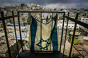 An Isreali flag hangs in the patio of a small jewish settlement in Hebron. The settlement is surrounded by Arab occupied buildings.