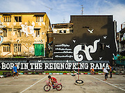 "01 DECEMBER 2016 0 BANGKOK, THAILAND: Boys ride their bikes around the takraw court in Chalermla Park (Graffiti Park) in Bangkok. The east wall of the park was repainted with a large mural that says ""Born in the reign of King Rama 9,"" with the nine written in Thai script. Bhumibol Adulyadej, the Late King of Thailand, was known as Rama 9. The park was repainted in his honor after his death on Oct 13.    PHOTO BY JACK KURTZ"
