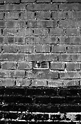 Beijing, China - July 2005 - A migrant worker looks through a hole in a wall surrounding a construction site in Beijing.