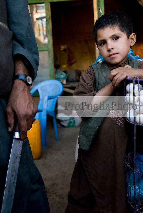 Helmand, 25 Sept. 2006. Shopkeeper and son in Lashkargah City