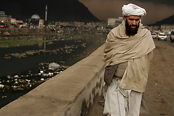 A bearded man walks along the Kabul river in Kabul, Afghanistan.