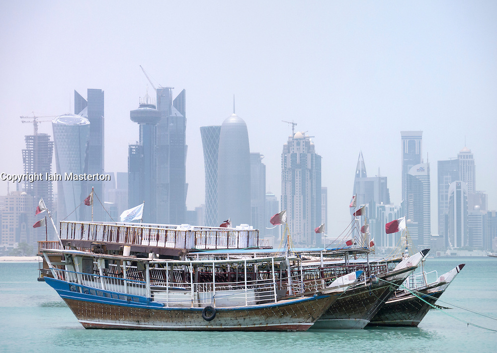 View of Dhows and modern skyline with skyscrapers in business district of Doha Qatar