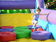 Bella Irvin, 3 of Morrisville, Pa. plays on an inflated obstacle course during the annual first Fourth event at Newtown Middle School Saturday July 11, 2015 in Newtown, Pennsylvania. The celebration was held a week late this year cause fireworks company couldn't make it on July 4th. (Photo by William Thomas Cain)