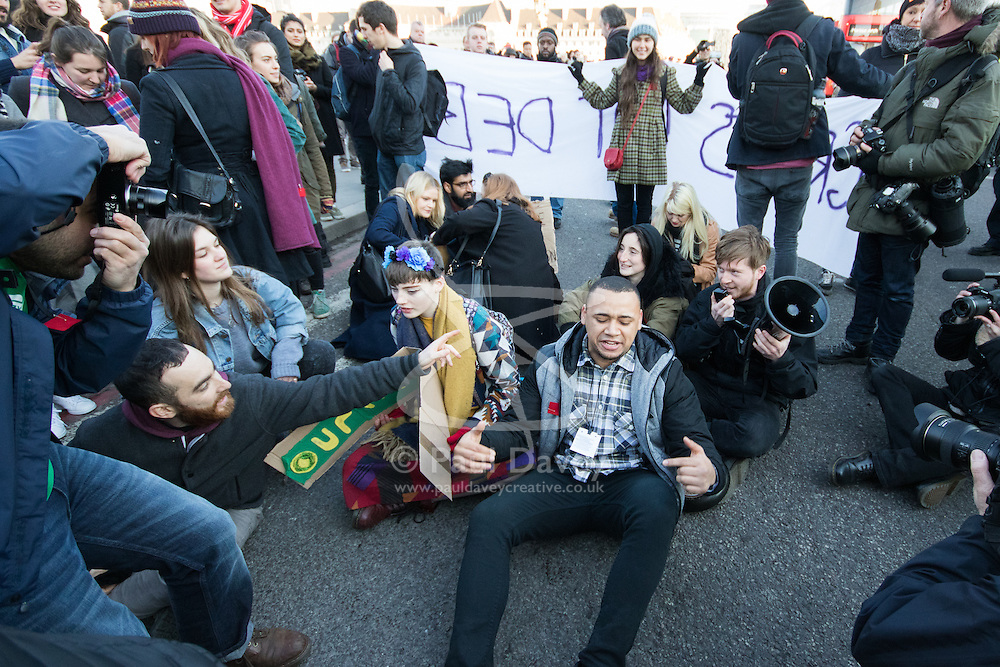 """Westminster, London, January 19th 2016. Students hold an """"emergency protest"""" in Parliament Square and later blocking Westminster Bridge, against the cutting of maintenance grants. """"It took just 18 MPs 90 minutes to scrap maintenance grants for the million poorest students, without a debate in Parliament in a backroom committee"""" PICTURED: Protesters stage a sit-in on Westminster Bridge. ///FOR LICENCING CONTACT: paul@pauldaveycreative.co.uk TEL:+44 (0) 7966 016 296 or +44 (0) 20 8969 6875. ©2015 Paul R Davey. All rights reserved."""