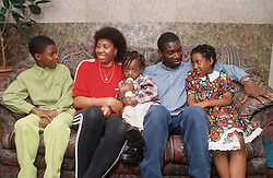 Portrait of couple and young children sitting together on sofa,