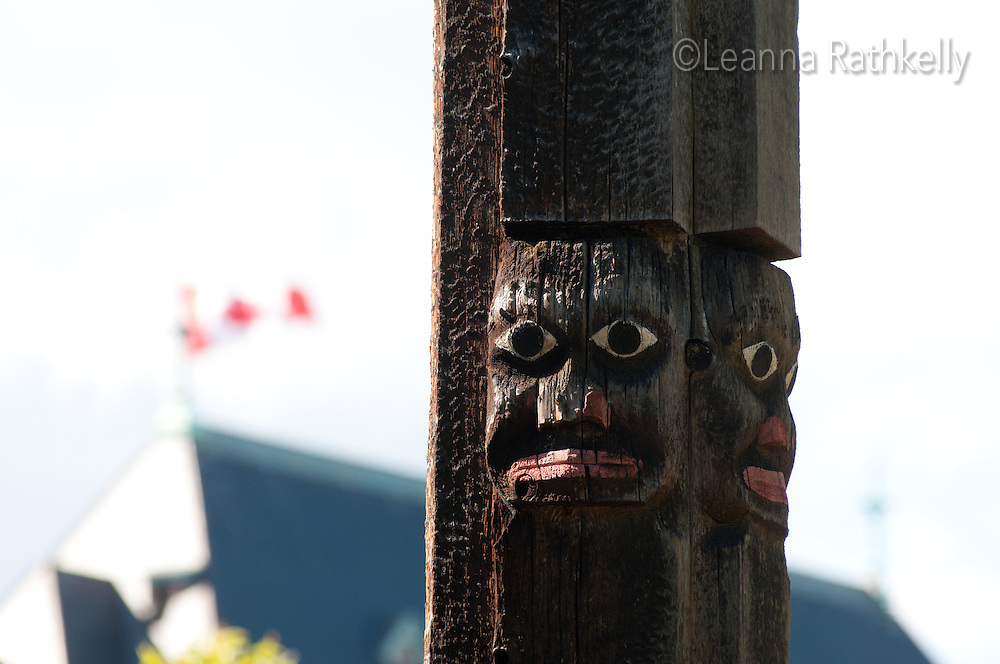 Totem poles rise high above the rooftops in Thunderbird Park, Victoria, BC Canada