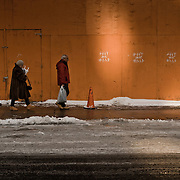 People walking in front of an orange fence and wall with nice colors.