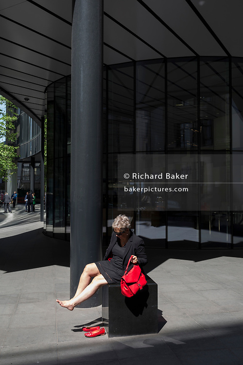 A woman rests her feet in a small area of sunlight on Fenchurch Avenue in the City of London - the capital's financial district, on 6th June 2018, in London, England.