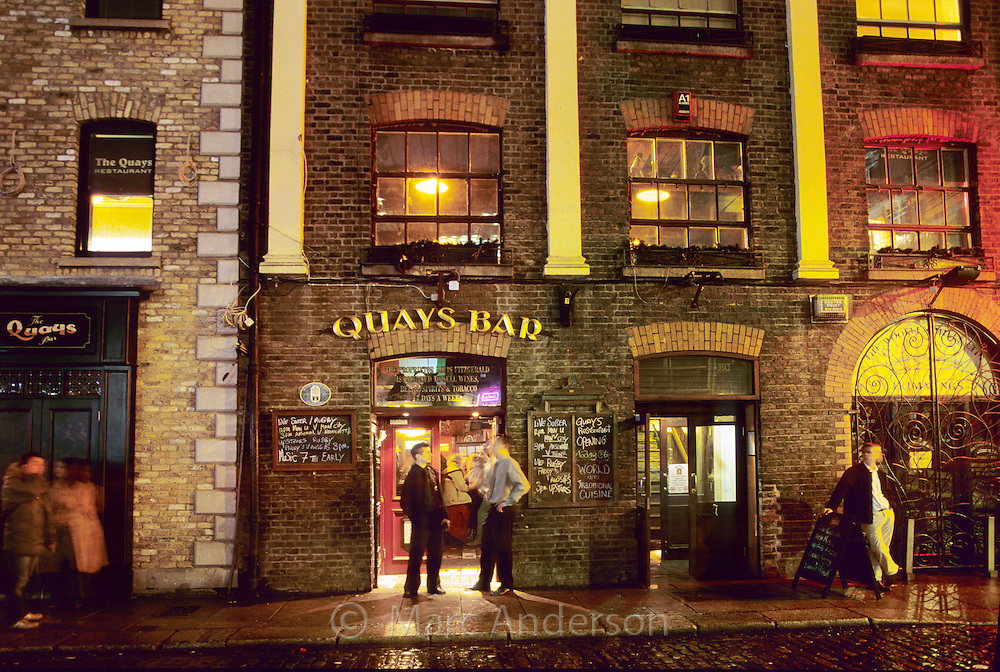 Men standing outside Quays Bar at night, Dublin, Ireland