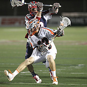 Drew Snider #23 of the Denver Outlaws keeps the ball away from a member of the Boston Cannons during the game at Harvard Stadium on May 10, 2014 in Boston, Massachusetts. (Photo by Elan Kawesch)