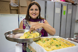 Image ©Licensed to i-Images Picture Agency. 07/03/2015. London, United Kingdom. Ravi Bhanot and family, Conservative Party supporters in Ilford. Ilford. Ravi's wife Sushma, arranges traditional indian food in a gathering at their local Hindu temple. Picture by Daniel Leal-Olivas / i-Images