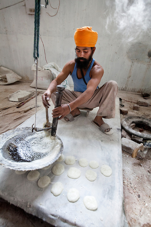 A Sikh cook prepares sweet cookies. The cookies are given to sikh pilgrims.