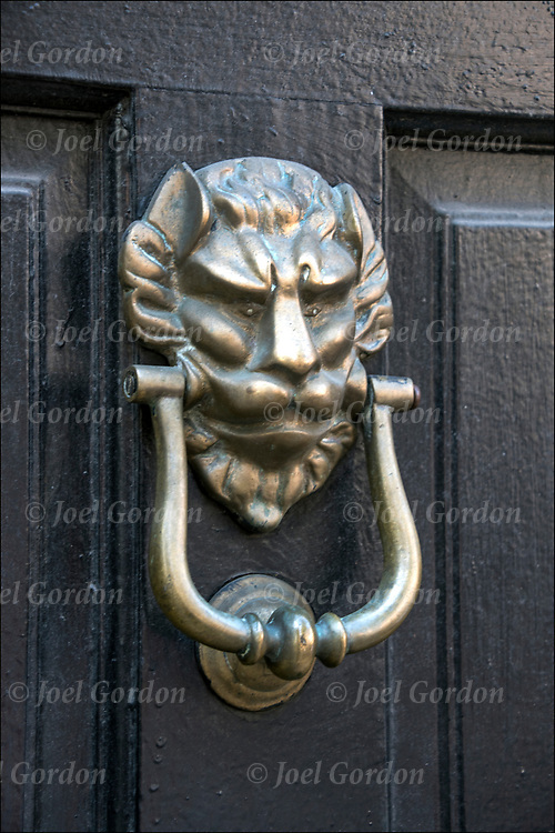 Decorative devil functional brass door knocker.