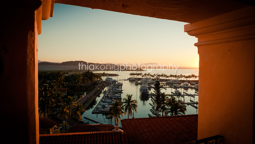 Looking out through arch to Grand Bay Hotel marina at sunrise, Barra de Navidad, Mexico