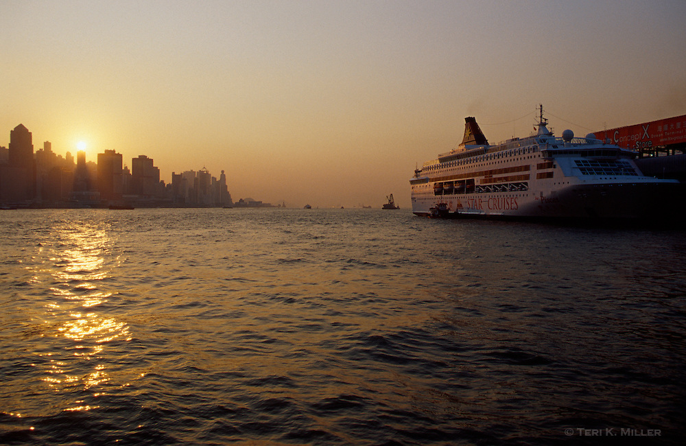 A cruise ship is docked in Victoria Harbour at sunset in Kowloon, Hong Kong, China.