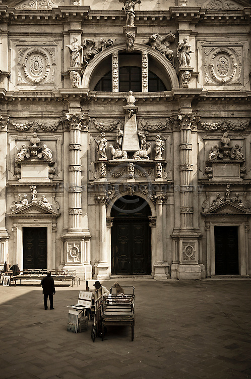 An artist and his dog in front of a church in Venice, Italy