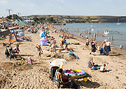 Crowded sandy beach families on summer holidays, Swanage, Dorset, England, UK