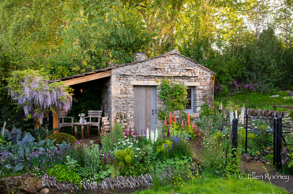 A cottage garden surrounding a stone bothy in the Welcome to Yorkshire Garden at the RHS Chelsea Flower Show 2018, London, UK