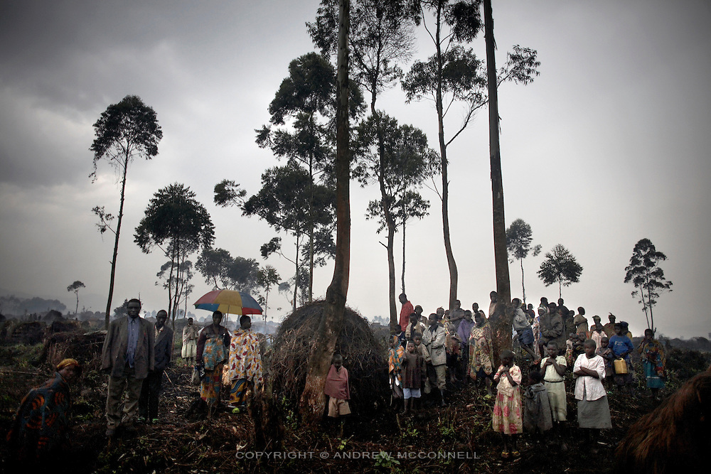 Displaced persons stand in the rain at the Chefferie IDP site, home to some 4,000 people, in the town of Kichanga, North Kivu, DRC.