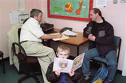 Professor sitting at desk in community paediatric health centre discussing child with parent and updating medical records,