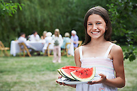 Girl (10-12) holding slices of watermelon in garden family members in background